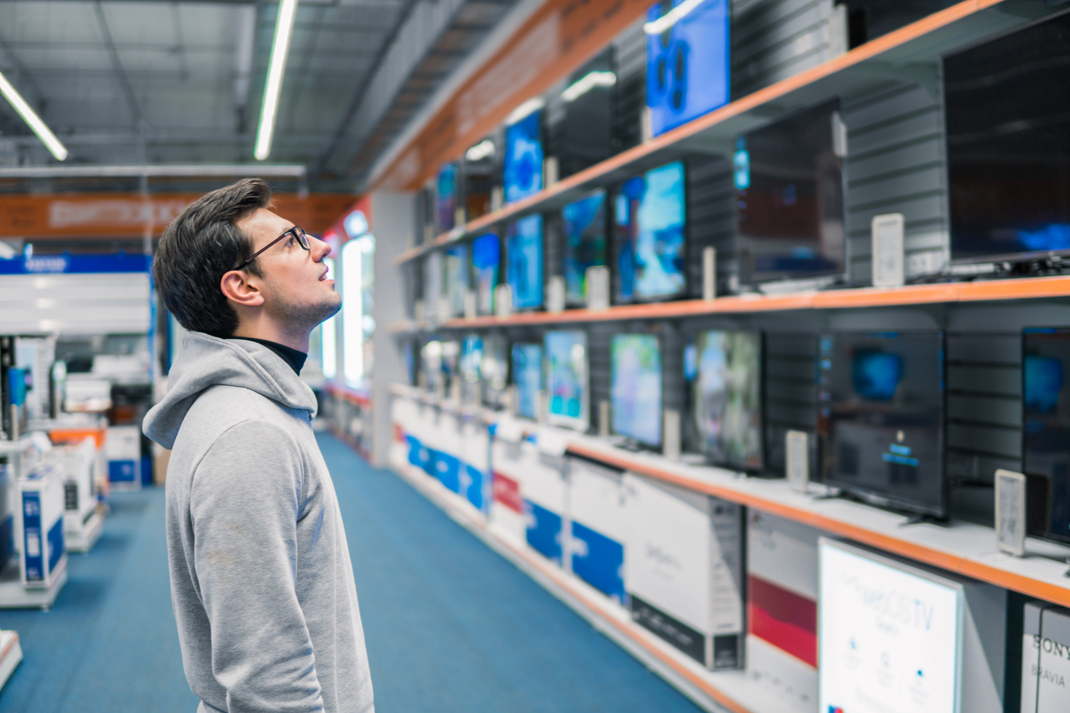 man in store looking at tvs